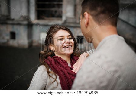 Smiling Girl With Braces. Young Couple Wearing On Tied Warm Sweaters Hugging In Love At Old Yard Wit