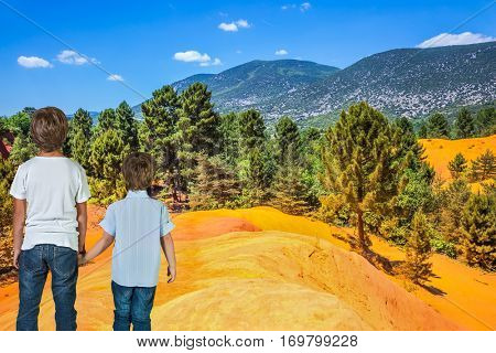 Two boys - brothers of seven and four years admire the magnificent nature. Orange and red picturesque hills in Languedoc - Roussillon, Provence, France