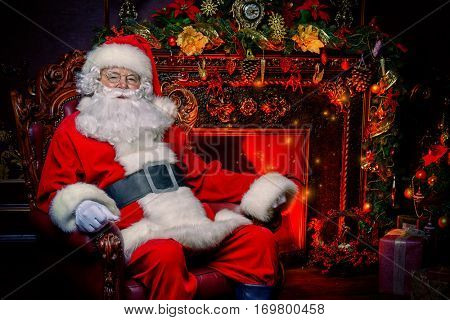 Santa Claus in his house next to the fireplace and Christmas tree resting in armchair.
