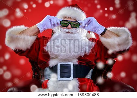 Portrait of cool modern Santa Claus wearing DJ glasses over red background. Christmas concept.