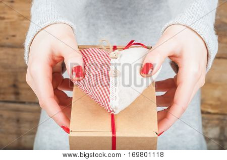 Hands holding gift in kraft box on a wooden background. The concept of St. Valentine's day weddings engagements Mother's Day birthday New Year Christmas holidays.