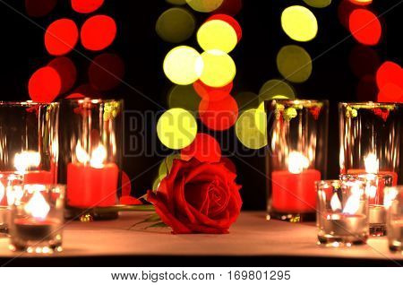 Beautiful red rose a concept of love and valentine's day put on a table with a candles in the glasses and blur round yellow and red bokeh of light bulb in the backgroung in the night