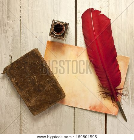 A square photo of sheet of aged paper with quill pen, bottle of ink, and old notebook, shot from above on a wooden background texture, slightly toned
