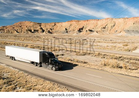 A black big rig rolls across Utah on a divided highway