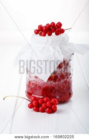 Schisandra chinensis or five-flavor berry jam on white. Five-flavor berries with sugar in a glass jar fresh red berries spread layers interspersed with sugar.