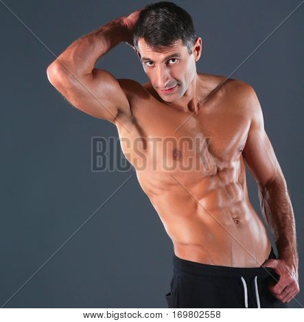 Strong athletic man standing on black background