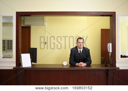 Smiling concierge behind the counter at his workplace in a luxury apartment building