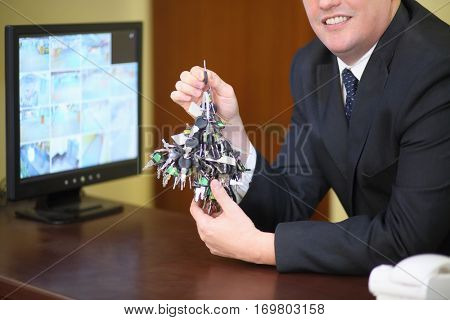 A large bunch of keys in the hands of a smiling concierge near the monitor with CCTV