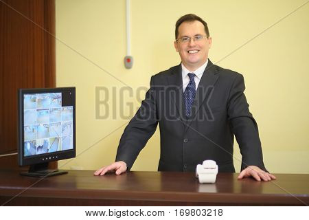 Concierge behind the counter at his workplace near the telephone in a luxury apartment building