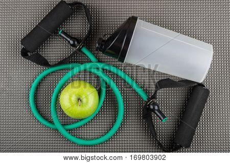 Rubber Tubular Expander, Green Apple And Plastic Shaker On Mat