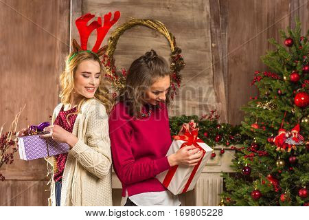 Excited young women opening christmas presents near christmas tree