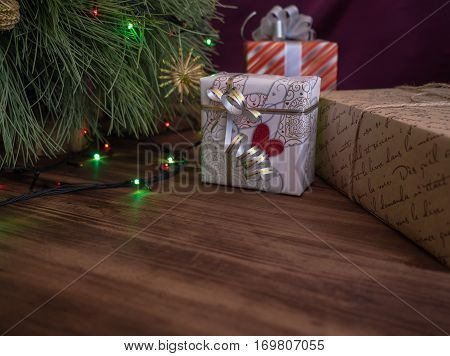 Green Christmas tree decorated with toys and garland with led lights. Boxes with gifts. Christmas present in boxes at wooden table. Green fir tree with toys and gifts under the tree.