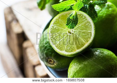 Heap of ripe organic limes cut in half in the sunlight, leaves of fresh mint, on vintage wood, ingredients for infused detox drinks, citrus, cleansing, diet