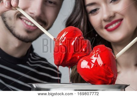 Fondue of love, loving couple dips chocolate hearts in red glaze