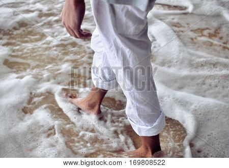 Male legs in sandy foam shore of ocean