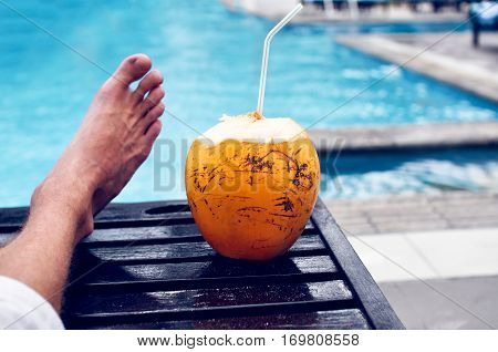 Man lazily resting by the pool with a drink of coconut