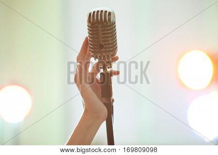 Female hand holding retro microphone, close up