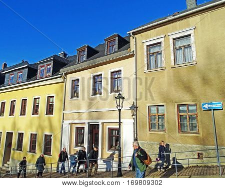 Annaberg-Buchholz, Germany - December 20, 2015: People walking up a steep road in the old town of Annaberg-Buchholz (Germany) along beautifully restored houses.