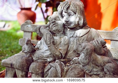 Art object on street: sculpture of two children with a dog on a bench