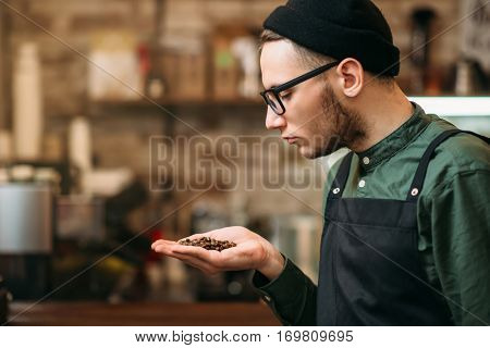 Barman holds in a palm grain of coffee