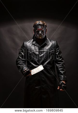 Bloody murderer in hockey mask with meat cleaver