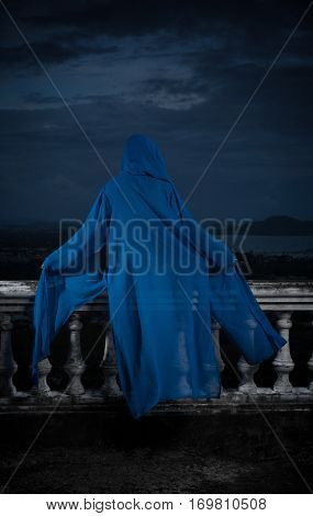 Back view of mysterious woman in black bikini and blue hoody cover up sitting on old stone ornate carved balustrade over cloudy sky and cityscape
