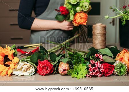 Florist with bouquet of roses at work.