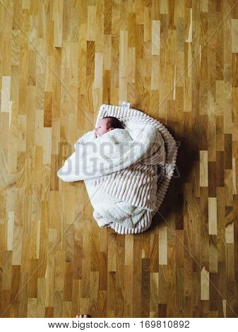 Baby wrapped in blanket lying on parquet floor
