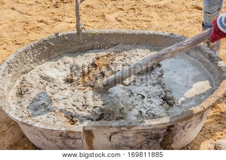 Concrete workers mixing and stirring the cement and sand in grunge steel salver building construction site.
