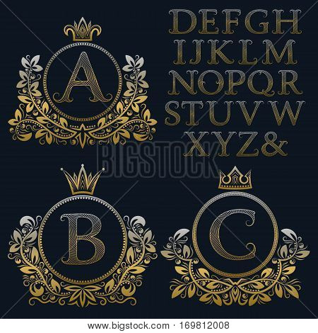 Vintage monogram kit. Golden patterned letters and floral coat of arms frames for creating initial logo in antique style.