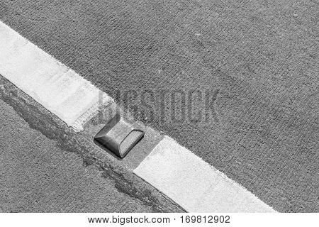 road stud reflector marker on concrete road with traffic line in black and white tone