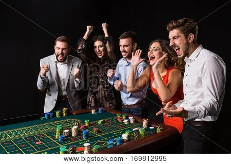 Group of young people behind roulette table on black background. Young people made bets in the game and wait for the result. Bright emotions poster