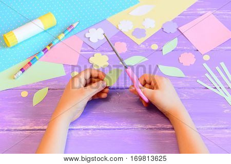 Small child does a greeting card for mom. Child holds scissors in hand and cuts a leaf from paper. Colored paper, paper templates, glue stick, pencil on a table. Mother's day or March 8 easy crafts