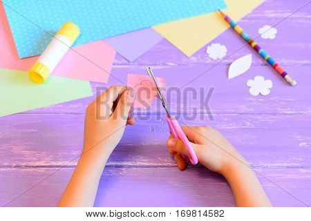 Small kid makes a greeting card for mom. Kid holds scissors in hand and cuts a flower from paper. Colored paper, paper templates, glue stick, pencil on a table. Mother's day or March 8 crafts concept