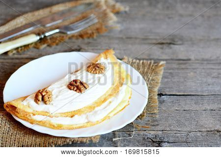 Cottage cheese omelette on a white plate. Delicious omelette stuffed with cottage cheese and walnuts. Vintage wooden background with copy space for text