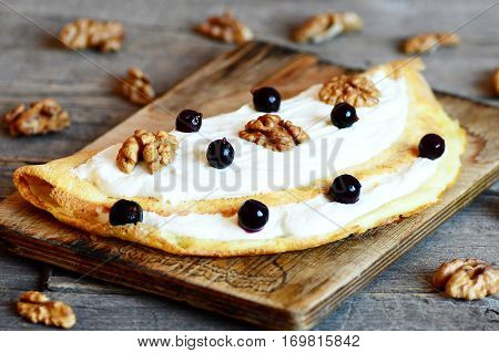 Omelet stuffed with soft curd cream, walnuts and black currants on a wooden board and vintage background. Delicious homemade omelet recipe. Closeup