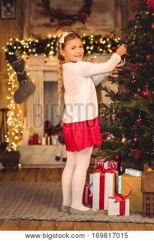 Smiling girl decorating christmas tree and looking at camera