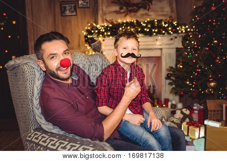 Happy father and son having fun and looking at camera at christmastime