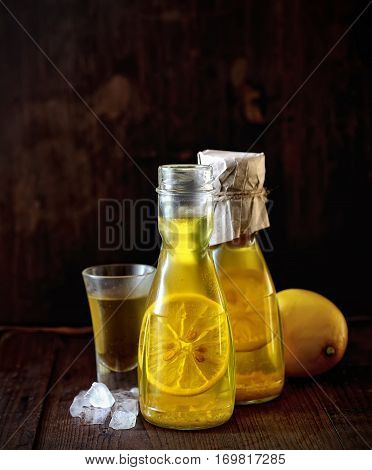 Limoncello in a bottle on a wooden background.Tradtitional italian homemade lemon beverage.