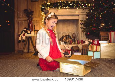 Excited girl sitting on carpet and opening christmas present