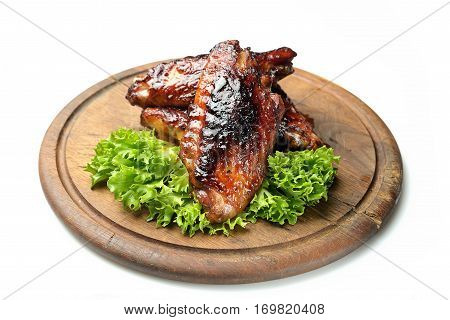 roasted turkey wings garnished with fresh green salad on the plate on white background