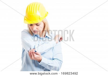 Female Architect Wearing Helmet Checking Her Elbow For Injures