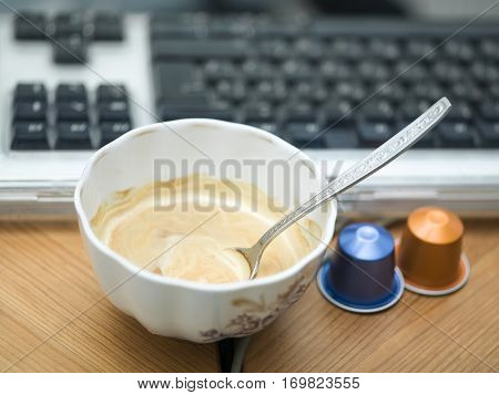 Cup of fresh espresso next to coffee machine capsules and a computer keyboard in the blurred background