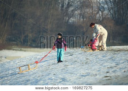 ZAGREB CROATIA - JANUARY 15 2017 : Children sledding down the hill in the presence of an adult woman at winter time in Zagreb Croatia.