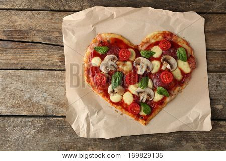 Tasty pizza in heart shape on parchment