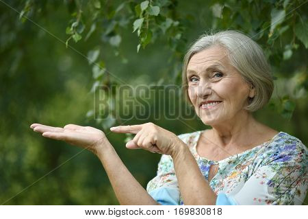 Older woman pointing on a nature background