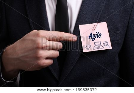 Business, Technology, Internet And Network Concept. Young Businessman Shows The Word: Agile