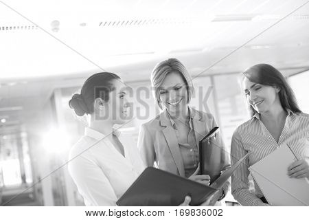 Businesswomen with file folders discussing in office