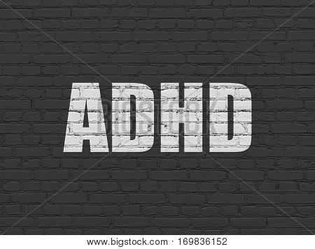 Healthcare concept: Painted white text ADHD on Black Brick wall background