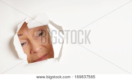 curious older woman looking through hole torn in white paper background at copy space. panoramic 16:9 banner or header format.
